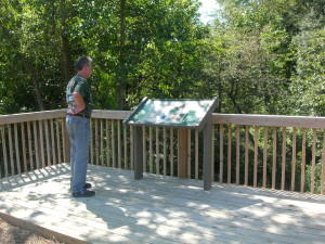 Indian Head Rail Trail user viewing Port Tobacco Headwaters interpretive sign